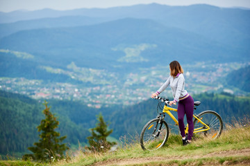 Athlete young woman cyclist with her yellow bicycle on a rural trail enjoying evening view of mountains, forests and small city on the blurred background. Outdoor sport activity. Copy space
