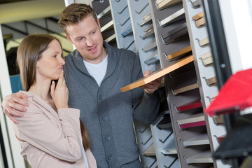 young couple standing in decoration store with tile color samples