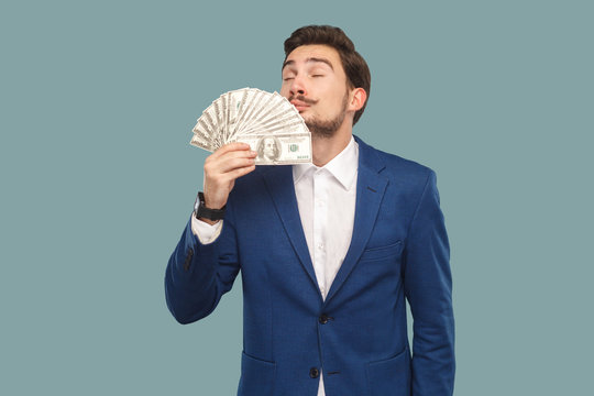 Handsome businessman in blue jacket standing and holding many dollars in hand and smelling and feeling smell of richness with closed eyes. Indoor, studio shot isolated on light blue background.