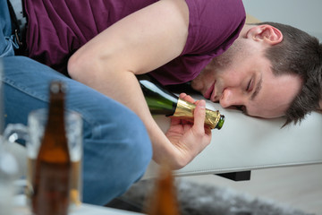 Inebriated man asleep holding empty wine bottle