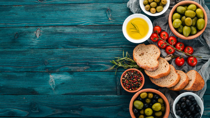 A set of green olives and black olives, and snacks. On a blue wooden table. Free space for text.