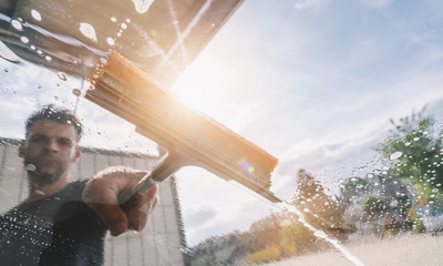 Man worker washing car with squeegee. car wash concept image. copyspace for your individual text.