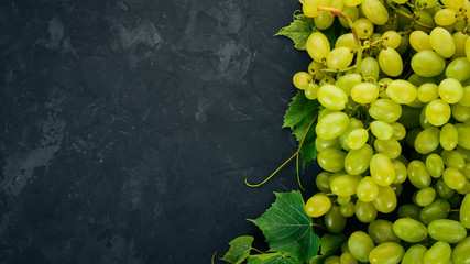 Green grapes with leaves of grapes on a stone table. Top view. Free space for text.