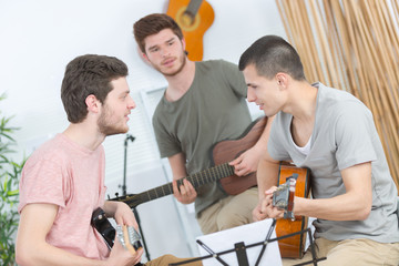 three friends rehearsing with guitar