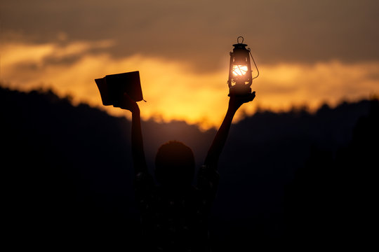Children holding oil lamp and holy bible with light sunset background. silhouette concept