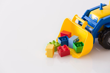 Children toy tractor with colorful plastic bricks on white background. Baby's toys on the table isolated.