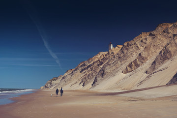 A couple takes a romantic walk at the danish beach with cliffs and sand dunes during summer holidays. Rubjerg Knude Lighthouse, Lønstrup in North Jutland in Denmark, Skagerrak, North Sea