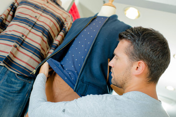Man dressing mannequin in shop