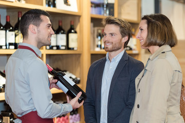 shopkeeper recommending wine to young couple