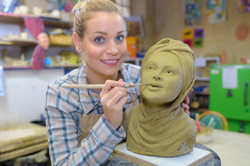 Artist making finishing touches to bust