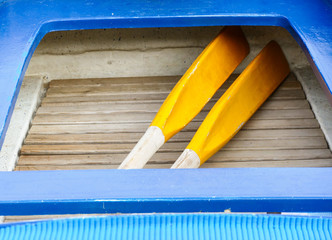 Blue little boat with yellow paddle