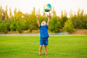 Little funny boy on stadium play football in summer day