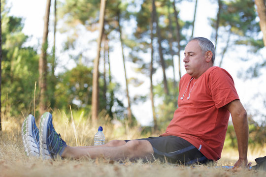 Middle aged man sat on ground while out exercising