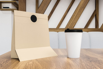 Breakfast in paper bag and coffee to go on table