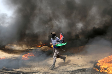 Demonstrator runs during clashes with Israeli troops at a protest where Palestinians demand the right to return to their homeland, at the Israel-Gaza border in the southern Gaza Strip
