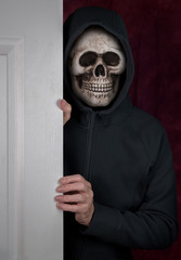Halloween theme of stalker with skull mask entering a home