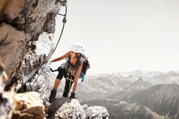 Foto op Plexiglas Alpinisme Fit sporty young woman mountain climbing