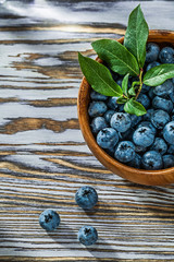 Juicy huckleberries in round wooden bowl