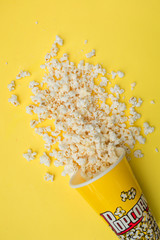 Container full of popcorn on yellow