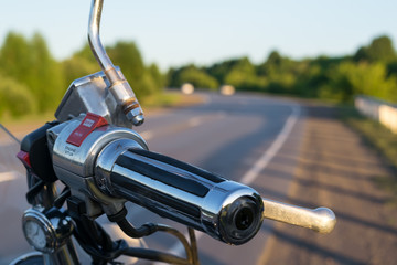view of handlebar grips of the motorcycle on the country road background closeup