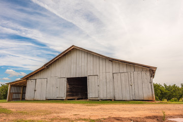 An old, beautiful barn that holds farm equipment stands regally on the side of the road in rural, upstate South Carolina. Bright blue sky and fluffy clouds behind.