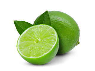 whole and half green lime with green leaves isolated on white background