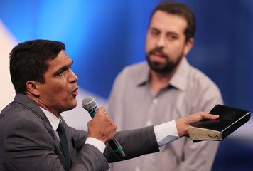 Presidential candidate Cabo Daciolo of Patriots holds the Bible next to candidate Guilherme Boulos of the Socialism and Freedom Party (PSOL) during a television debate at the Rede TV studio in Osasco