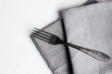 Steel fork and gray cloth napkins on a white wooden table