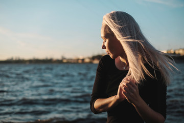 Lifestyle portrait of smilyng young blonde woman in windy day at sea, sunset light