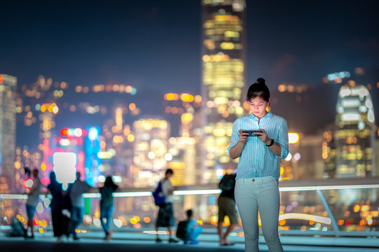 Woman using smartphone at night with Victoria Horbor in background