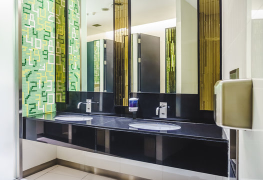 New modern restroom with touch-free automatic sensor faucets. It consists of new mirror, ceramic washbasins, granite countertop, liquid soap and toilet paper roll holder.