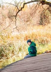 Boy sits on wooden bridge near the autumn pond