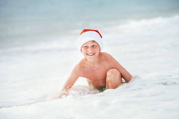 Happy boy in Santa's hat swims on ocean surfline. Christamas and NeawYear holiday on tropical islands