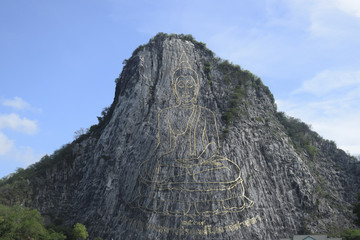 Golden Buddha carved on a cliff. God on the mountain.