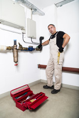Plumber repairing metallic water pipes with wrench