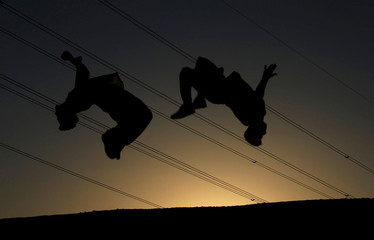 Iraqi youth, perform a somersault as they practice parkour in Najaf