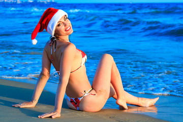 Sexy Santa's helper at the tropical beach, gorgeous woman enjoys her christmas vacations on sea resort. Evening light