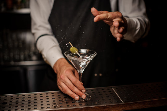 Bartender making a fresh and strong summer martini cocktail with olive and salt