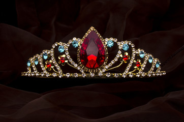 Wall Mural - gold diadem with red ruby stone isolated on the fabric