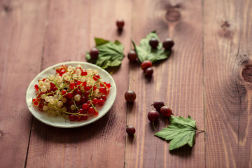 Berries of a currant, gooseberries on a saucer, leaves, on a natural wooden background