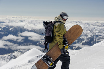 man in ski equipment, wearing safety glasses, rises to a snowy mountain against a cloudy sky Wall mural