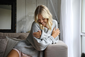 Hübsche blonde Frau kuschelt sich auf einem Sofa ein