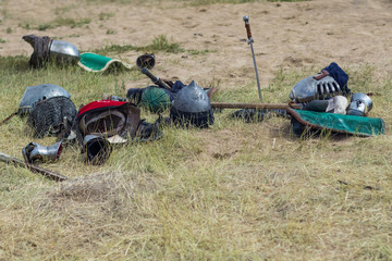 Knight armor lies on the grass after the end of the battle.