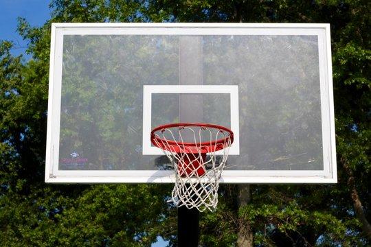 A glass backboard on the outdoors basketball hoop.