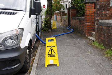 Mobile house cleaning van with caution signs and water pipe