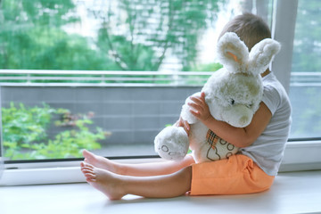 boy of two years sitting by the window and hugs a toy Bunny. rainy weather, waiting for dad to come home from work.