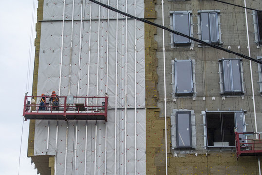 Construction of a hotel. Workers on suspended scaffolding