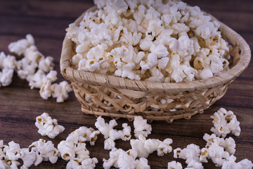Fresh cooked Salty popcorn on wooden background