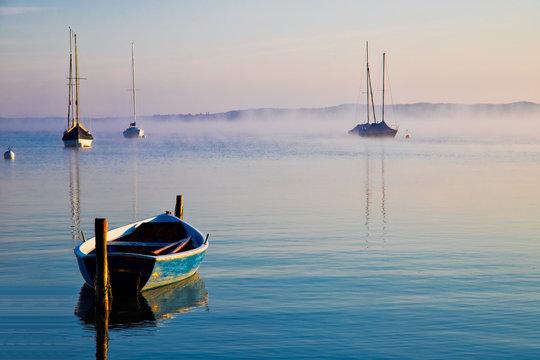 Morgendliche Seelandscahft mit Booten im Nebel