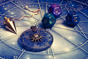 horoscope with zodiac signs, astrology dice, pendulum, sun astrology pendant and cars like esoteric concept
